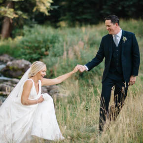 bride and groom at beaver creek wedding chapel, holding hands in tall grass, colorado wedding inspiration, mountain wedding planner, beaver creek weddings