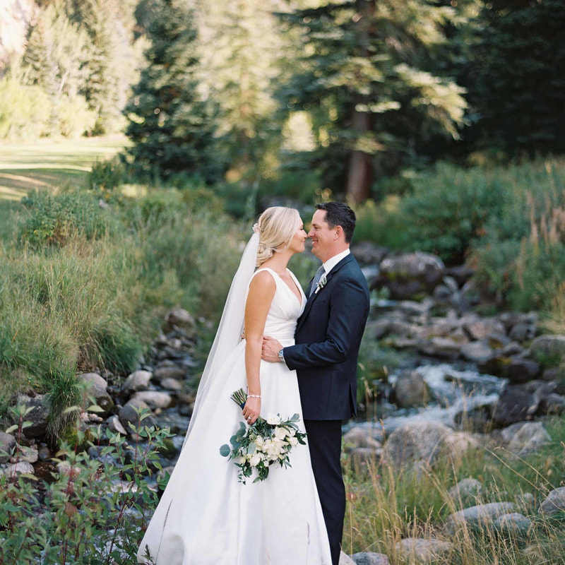 bride and groom portrait, groom kissing bride's forehead, beaver creek chapel wedding, couples portraits along creek, mountain wedding inspiration, colorado wedding planning, sweetly paired planners