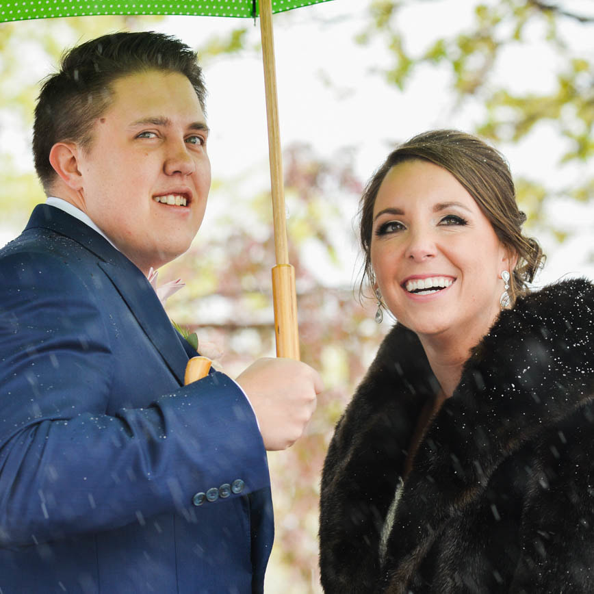 Bride and groom portrait in the snow under green umbrella, cherry blossoms in the snow, baldoria on the water wedding venue, denver wedding planner, colorado wedding planner, real weddings, sweetly paired, winter wedding inspiration