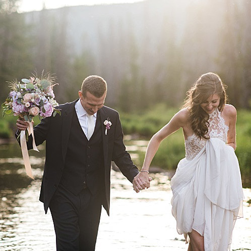bride and groom walking holding hands in mountain lake, glamping wedding, piney river ranch wedding planner, vail wedding planner, mountain wedding inspiration, colorado real weddings