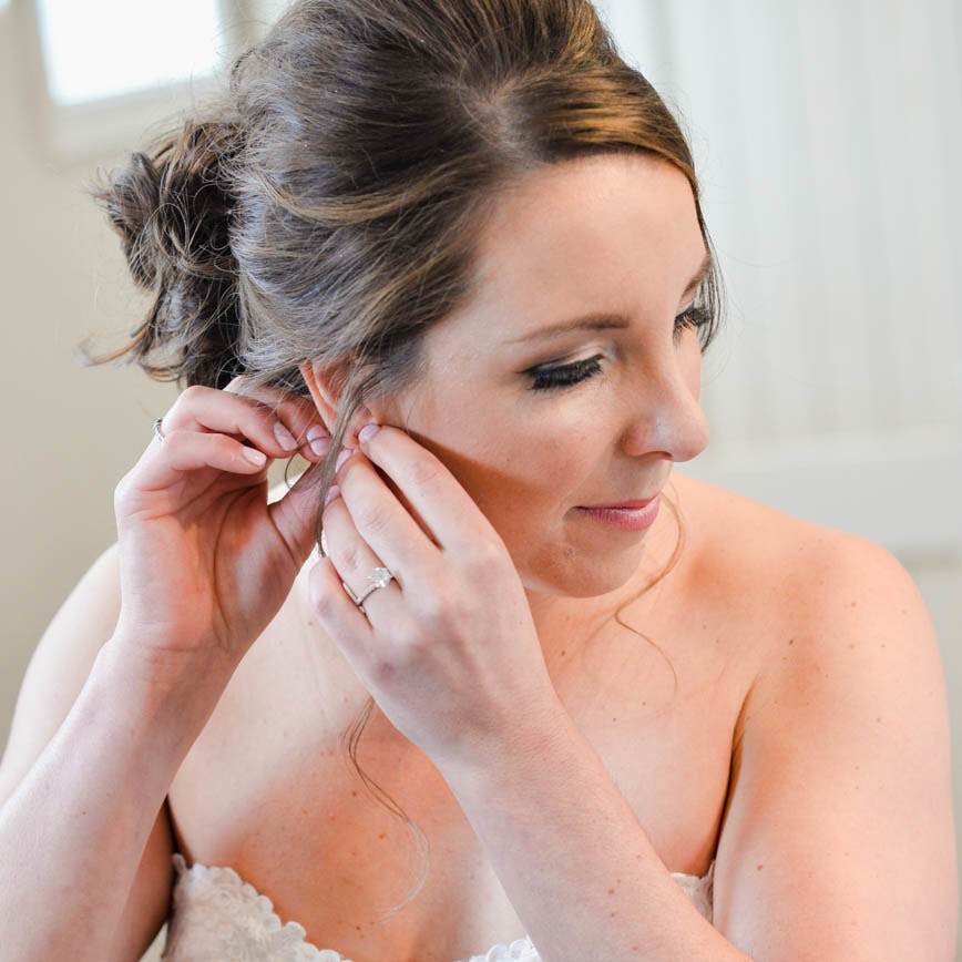 Bride getting ready photo, putting on diamond earrings, bridal up do, detail photos, denver wedding planner, colorado wedding planner
