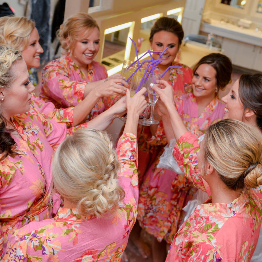 Bride getting ready photo, putting on dress, detail photos, denver wedding planner, colorado wedding planner, bride and bridesmaids in pink floral robes, champagne toast, bridal hair up do