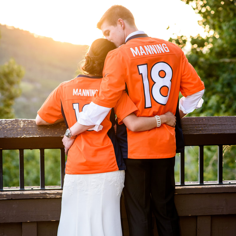fun Bride and groom portrait wearing broncos jerseys, allie's cabin, mountain top wedding, beaver creek wedding planner, colorado wedding planner, sweetly paired, mixed race couple, asian bride