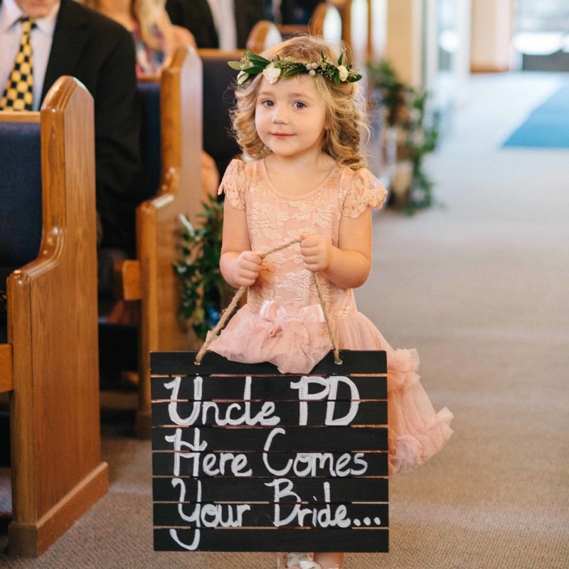 beaver creek chapel ceremony, flower girl walking down the aisle with wooden sign, uncle pd here comes your bride, flower crown and pink dress, colorado mountain wedding, beaver creek wedding planning, sweetly paired wedding planners