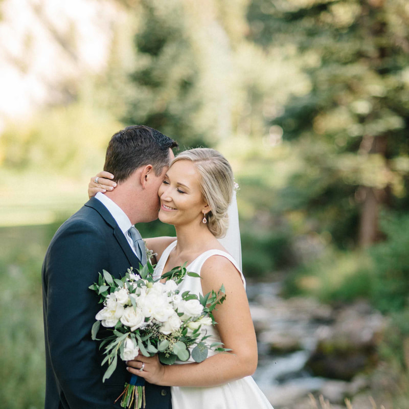 bride and groom portrait along creek outside beaver creek wedding chapel, park hyatt beaver creek, mountain wedding inspiration, white and green bouquet, sweetly paired wedding planner