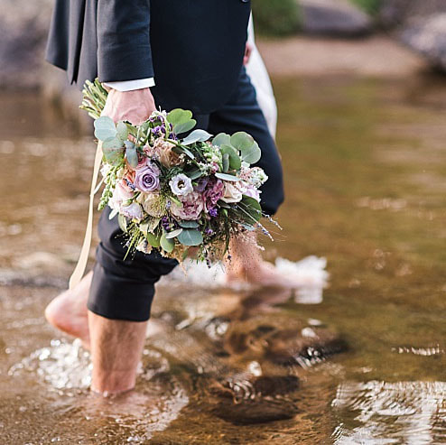 wedding mountain inspiration, beaver creek wedding planner, vail wedding planning, sweetly paired weddings, bridal bouquet, pastel color palette, lavender and blush wedding colors, groom walking in lake barefoot holding bouquet