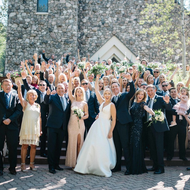 beaver creek chapel group photo on steps after wedding ceremony, bride and groom surrounded by wedding guests cheering, mountain wedding inspiration, colorado wedding planning